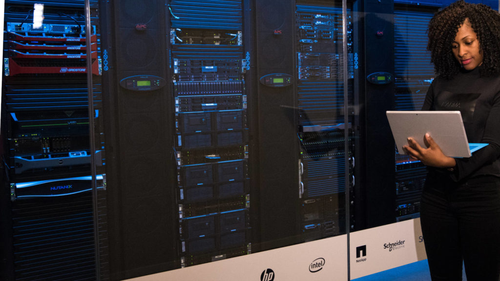 person looking at a laptop with server racks in background